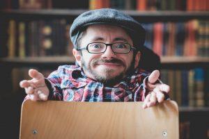 Raul schaut mit geöffneten Händen in die Kamera über einen Stuhl gebeugt.