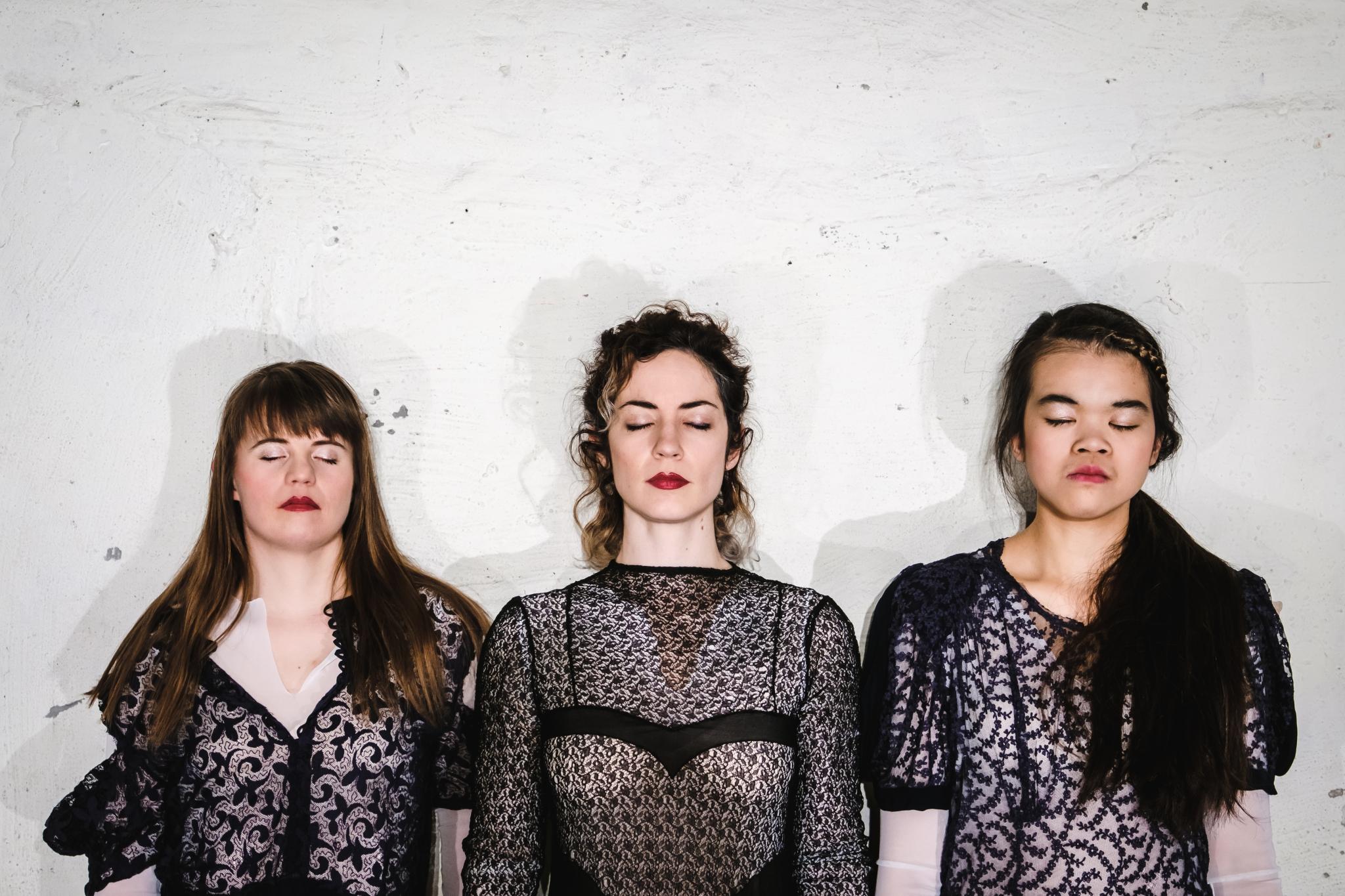 Drei Frauen stehen mit dem Rücken zur Wand. Nebeneinander. Ihre Körper und Gesichter sind dabei Richtung Kamera gerichtet. Ihre Augen sind geschlossen.
