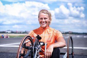 Ein Bild von Christiane Reppe auf dem Handbike, die in die Kamera lächelt