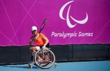 Paralympics-Sportlerin Marjolein Buis mit Tennisschläger im Rollstuhl vor Paralympics-Plakat in London 2012