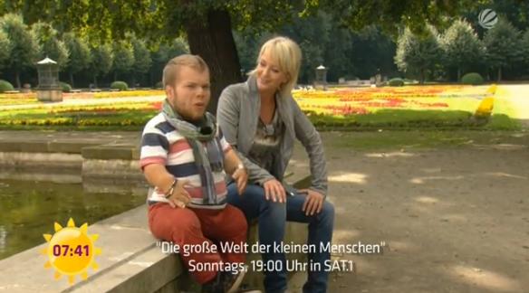 Screenshot von einer Moderationssituation von Michel Arriens und Ulla Kock am Brink. Beide sitzen nebeneinander auf einem Gemäuer und moderieren.