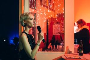 Gründerin Denise Linke auf der Release-Party des Nummermagazins. Sie hat kurze blonde Haare, ein schwarzes enges Abendskleid und ein Mikrofon in der Hand.