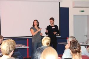 Claudia Piplow und Dominik Batram, Kommunikationsworkshop für schwerhörige und hörende Berufstätige im Umgang miteinander. Beide Trainer stehen vor einer Gruppe und reden.