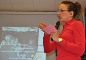 Claudia Piplow während eines Workshops . Sie trägt offen sichbar ihre grünen Hörgeräte.
