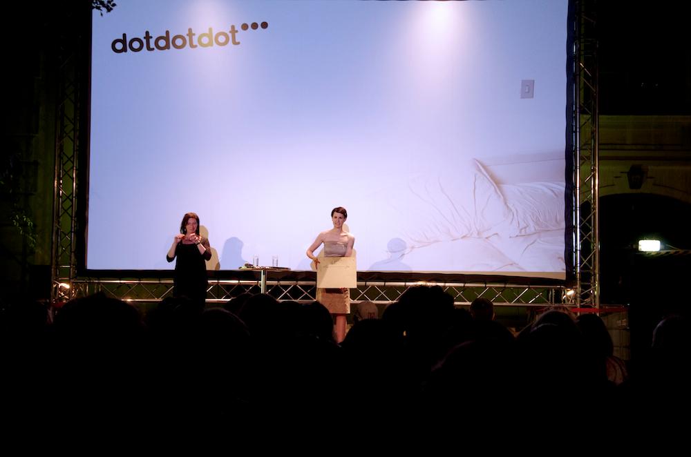 Weiße Leinwand vom dotdotdot Open Air Kurzfilmfestival. Darauf der Schriftzug dotdotdot mit drei schwarzen Punkten. Davor steht die Festivalleiterin Lisa Neumann und spricht, neben ihr eine Gebärdensprachdolmetscherin.