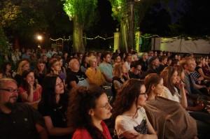 Zuschauerinnen und Zuschauer einer Filmvorführung auf dem dotdotdot Open Air Kurzfilmfestival in Wien. Im Hintergrund bunte Lichter und Bäume bei Nacht.