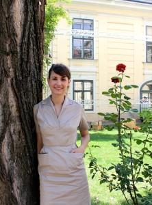 Foto von der Festivalleiterin Lisa Neumann. Sie steht im Garten vor dem gelben Gebäude des Volkskundemuseums, neben ihr eine rote Rose. Sie trägt dunkelbraune Haare zum Zopf gebunden und ein elegantes beigefarbenes Kleid mit Kragen, ohne Ärmel und seitlich zwei kleinen Taschen auf der Hüfte. Sie lächelt in die Kamera.