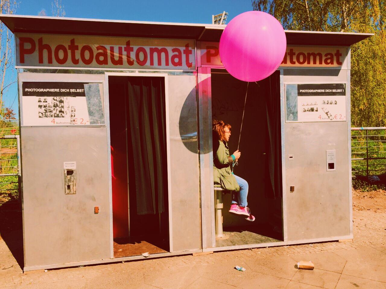 Ninia Binias sitzt in einem alten Photoautomaten und hält einen pinken Luftballon in der Hand