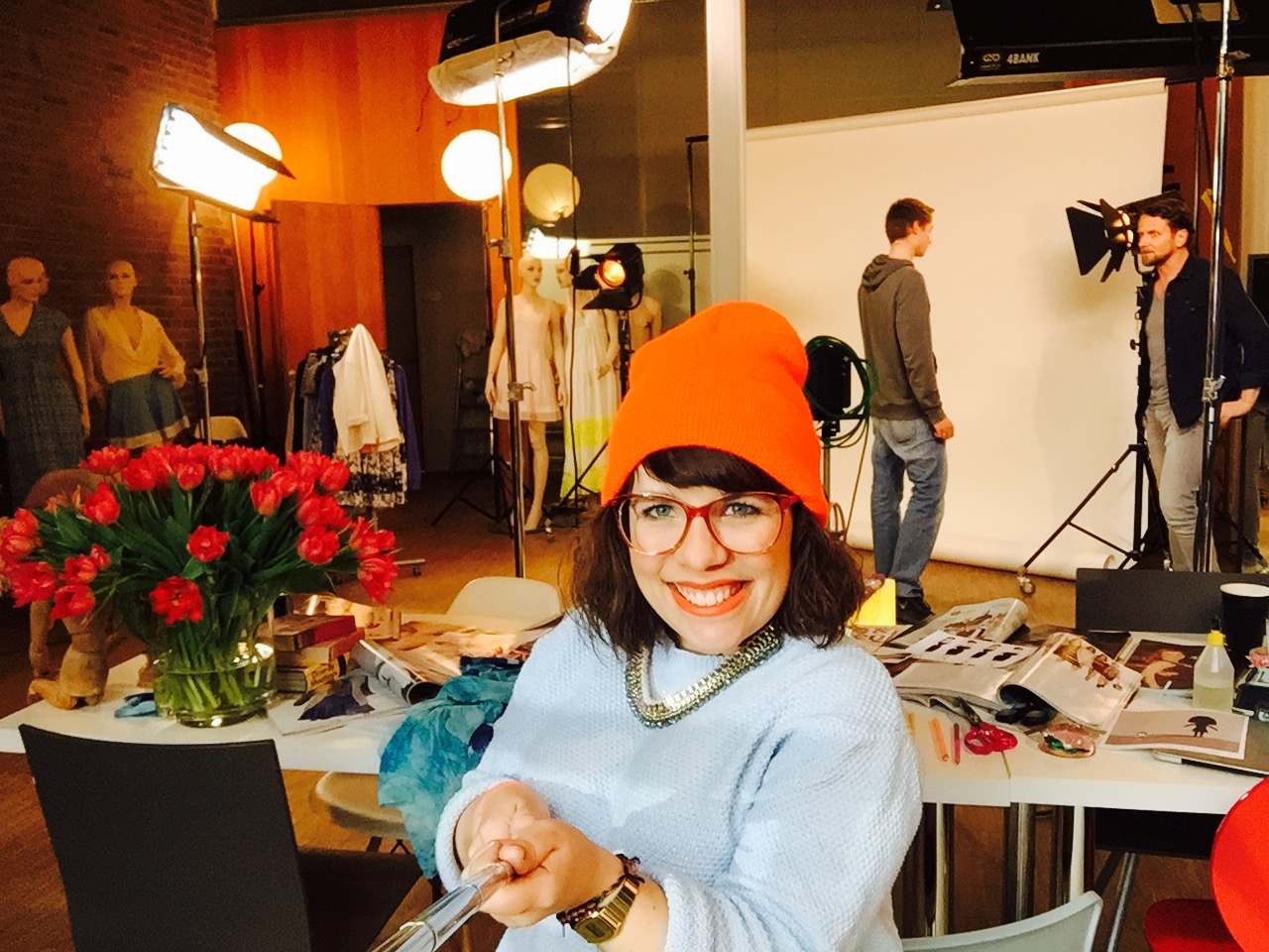 Ninia Binias als Moderatorin im Studio von RTL für Aufnahmen zum Fashionmag. Sie trägt eine rote Mütze, rote Brille, helleblauen Pullover und lacht in die Kamera. Im Hintergrund arbeiten Kameraleute am Set.