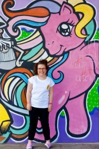 Ninia Binias steht vor einer Graffiti-Wand. Im Hintergrund ein pinkes Einhorn mit bunten Haaren aufgemalt. Ninia trägt ein weißes T-shirt, schwarze Hose, pinke Schuhe und rote Brille.