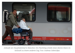 Ein Mann schiebt einen Mann im Rollstuhl. Hinter ihnen ein Zug der Deutschen Bahn. Beide Männer sind Flüchtlinge und befinden sich am Münchner Hauptbahnhof.