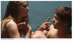 Sergej und Anna liegen nackt nebeneinander und unterhalten sich in der Gebärdensprache. Im Hintergrund eine blaue Wand.