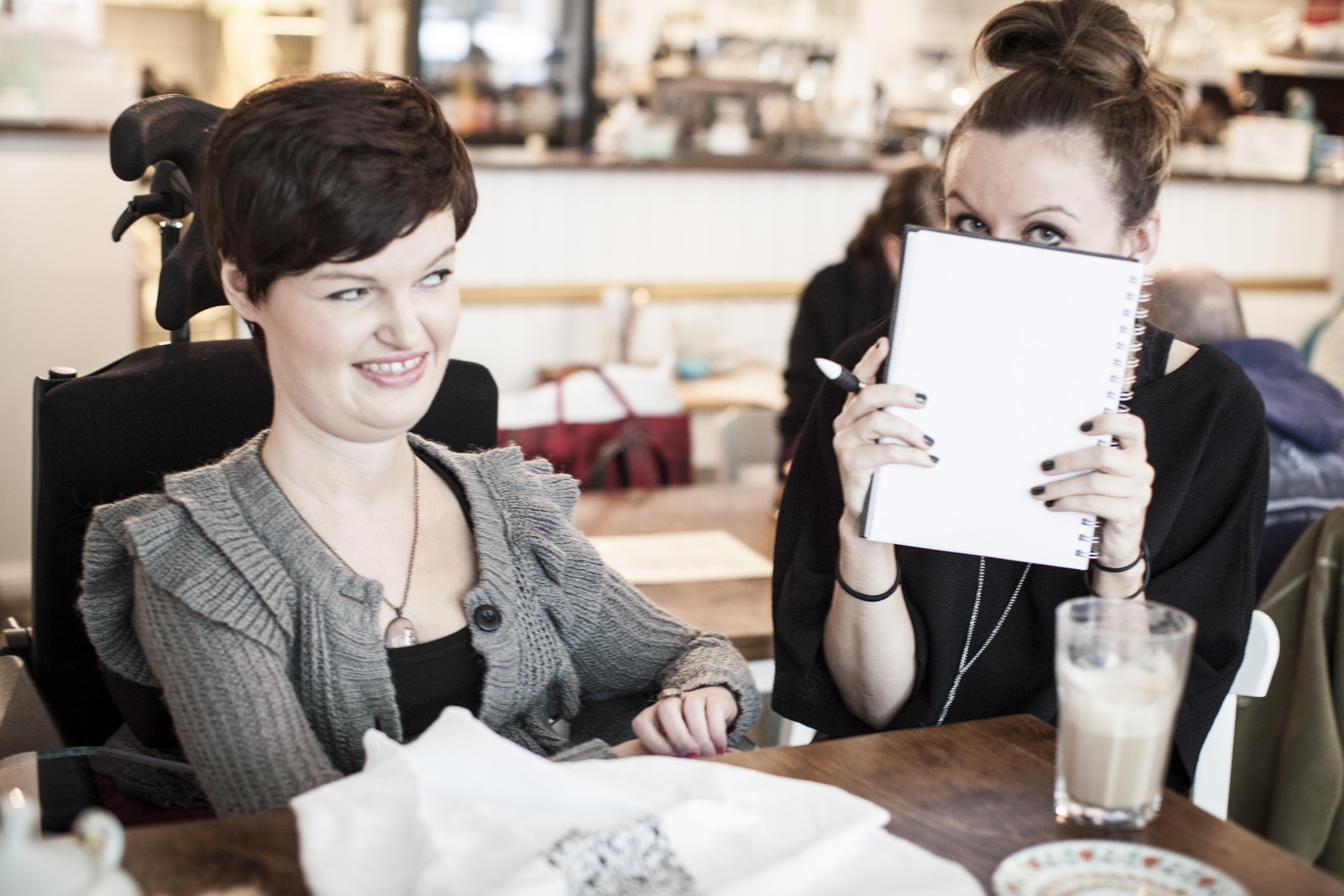 """Anastasia Umrik sitzt mit ihrer Kollegin Kathrin Neumann von """"inkluWAS"""" in einem Café. Anastasia Umrik trägt eine hellgraue Wolljacke und eine elegante Kette und lächelt aus dem Augenwinkel ihrer Kollegin zu. Kathrin Neumann hält trägt einen schwarzen Pullover und schwarz lackierte Fingernägel und hält einen Schreibblock so über ihr Gesicht, dass man nur ihre schwarz geschminkten Augen sieht."""