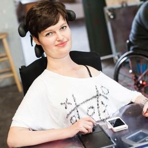 Anastasia Umrik sitzt an ihrem Schreibtisch, trägt ein weißes T-shirt, dass ihre linke Schulter zeigt und vorne ein aufgemaltes Bingo-Spiel. Sie lächelt in die Kamera,. Vor ihr liegt ein weißes iphone .