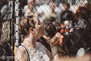 Aktivistin im Käfig pustet Seifenblasen.