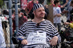 """Matthias Grombach sitzt im Käfig in einem schwarz-weiß gestreiften Gefangenen-Kostüm. Er trägt ein Plakat mit der Aufschrift """"Daheim statt Knast (Heim)"""""""