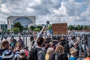 """Eine Gruppe von Menschen in dem Käfig und ein Plakat mit """"Ich pfeife auf euer (Spar)Gesetz, echte Teilhabe jetzt!"""". Hintergrund Kanzleramt."""