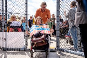 """Aktivistin rollt aus dem Käfig. Sie trägt ein Plakat mit der Aufschrift """"Für ein UN-konformes BTHG""""."""