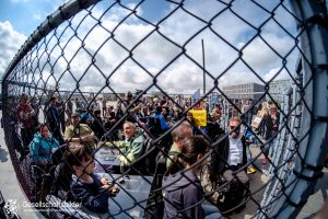 Blick in den Käfig von außen auf die Aktivist*innen. Technik des Fotos Fischeye-Objektiv.