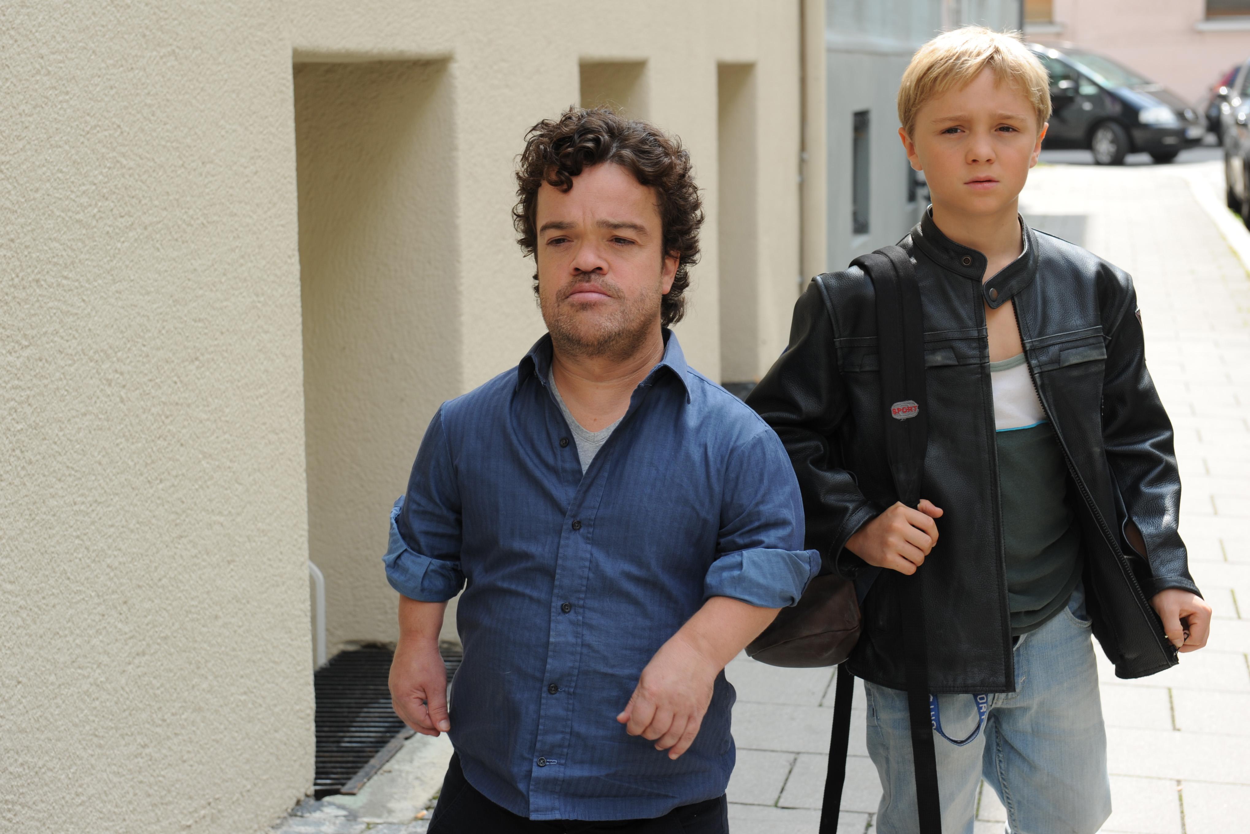 Michi und sein Vater Tom laufen über die Straße. Ihre Gesichter sind ernst. Tom trägt ein blaues locker hochgekrempeltes Hemd. Michi eine schwarze Lederjacke und einen Rucksack.