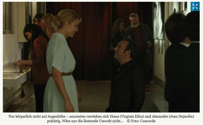 """Alexandre und Diane stehen sich auf einer Veranstaltung gegenüber und lächeln sich an. Sie trägt ein weißes chiques Kleid, er ein schwarzes Hemd. Der Untertitel des Bildes lautet: """"Nur körperliche nicht auf Augenhöhe - ansonsten verstehen sich Diane (Virigine Efira) und Alexandre (Jean Dujardin) prächtig. Wäre nur die lästernde Umwelt nicht..."""""""