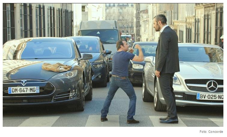 Alexandre (Jean Dujardin) und der Ex von Diane stehen auf einem Zebrastreifen. Alexandre trägt ein blaues T-shirt und blaue Jeans und hält ihm geballte Fäuste entgegen. Der Ex von Diane steht ihm verdutzt guckend in schwarzem Anzug mit weißem Hemd gegenüber. Hinter beiden stehen wartende Autos.