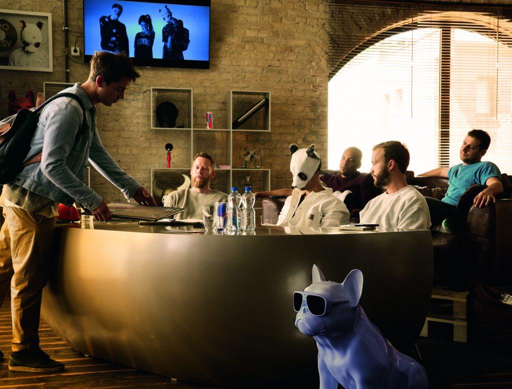 Drei Männer sitzten an einem großen Tisch, in der Mitte der Rapper Cro mit Pandamaske. Sie werden von einem Kellner bedient. Etwas abseits vom Tisch steht eine weiße Hundefigur (Mops). Der Hund trägt eine Brille