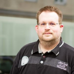 Aleksander Knauerhase ist bis zur Brusthöhe zu sehen. Er hat ein leichtes Lächeln auf den Lippen und trägt eine Brille. Außerdem ein schwarzes Shirt.
