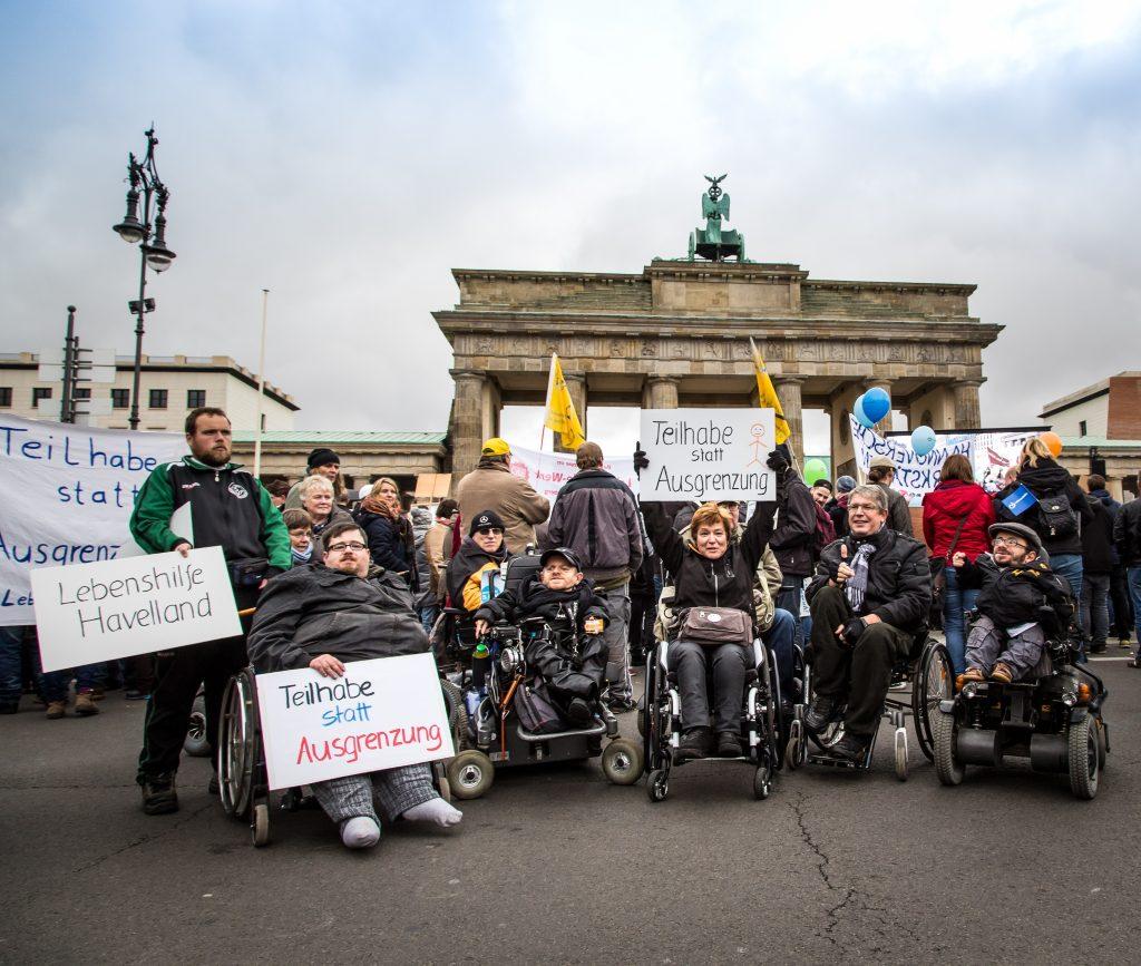 Ein Gruppenbild von Aktivist*innen mit Behinderung vor dem Brandenburger Tor.