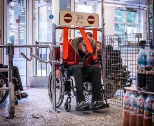 Ein älterer Herr im Rollstuhl möchte in den Supermarkt. Er zwängt sich am EIngang durch den Einlass für den Einkaufswagen. Sein Kopf ist tief nach vorne gebeugt, trotzdem berühren ihn die Plastikzungen von oben.