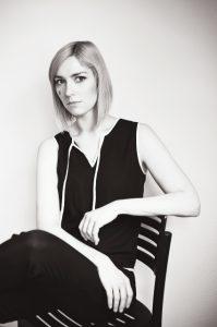 MArlies Hübner sitzt auf einem Stuhl. Sie hat blonde kurze Haare und dunkle Augen, sie trägt einen schwarzen Jumpsiut. Es ist ein Bild in schwarz-weiß.