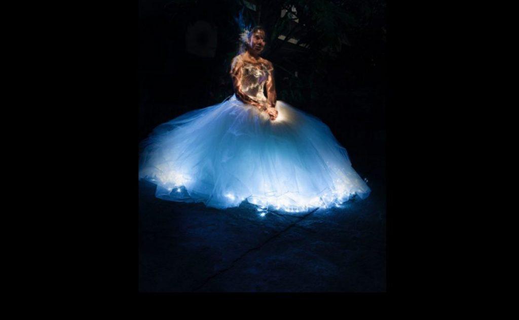 EIne Frau schwebt im Dunklen. Sie hat ein leuchtend blaues, weites Kleid an.
