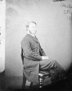 Eine Schwarz-Weiß-Fotografie aus dem 19. Jahrhundert. Ein junger Mann mit Down-Syndrom sitzt in chiquer Kleidung, also Stoffhose und Frack, auf einem Holzstuhl. Er trägt einen langen Bart auf beiden Seiten der Wange und hat die Haare im Seitenscheitel nach hinten gekämmt.