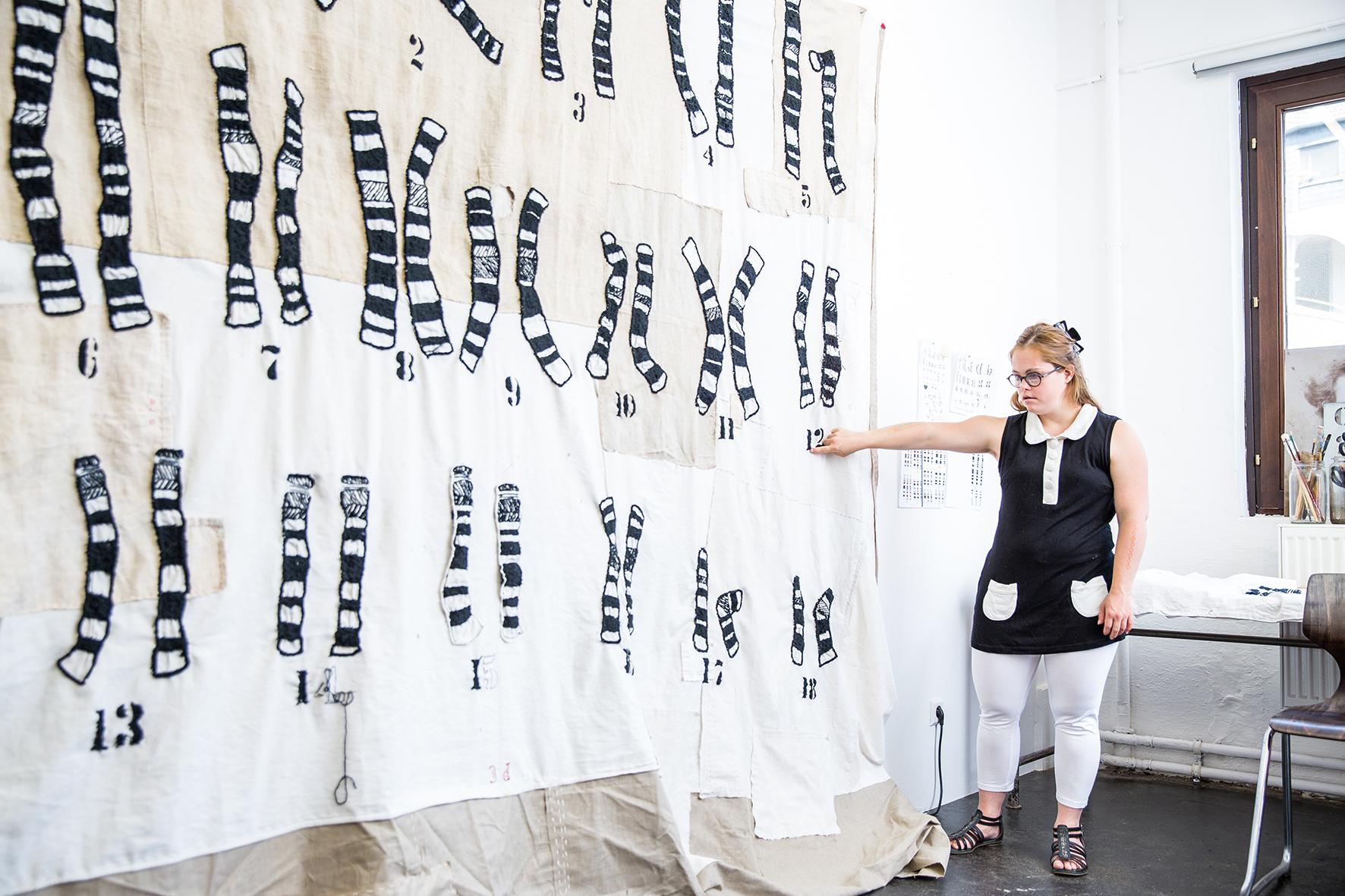 Eine Frau mit Down-Syndrom steht vor ihrem selbst genähten Wandteppich mit aufgenähten Chromosomen. Sie hat blonde lange Haare, trägt eine schwarze Brille, eine schwarz-weißes Bluse mit weißem Kragen und ohne Ärmel, eine weiße Hose und schwarze Sandalen. Auch die Chromosomen auf dem Teppich sind in den Farben schwarz und weiß.
