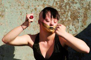Eine Frau mit Down-Syndrom steht mit geballten Fäusten und geschlossenen Augen vor einer türkis-braunen Wand. Über ihren Mund ist ein großer goldener Flügel gemalt, die Lippen sind grün geschminkt. Ihre Haare sind hinten abrasiert und ein schwarzer Pony fällt in die Stirn. Sie trägt ein schwarz-glitzerndes Top mit großem Ausschnitt und einen rot-glitzernden großen Ring.