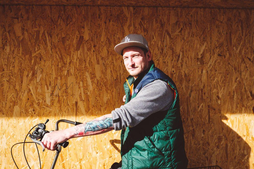 Porträt von Singer und Songwriter Graf Fidi vor einer gelben Holzwand