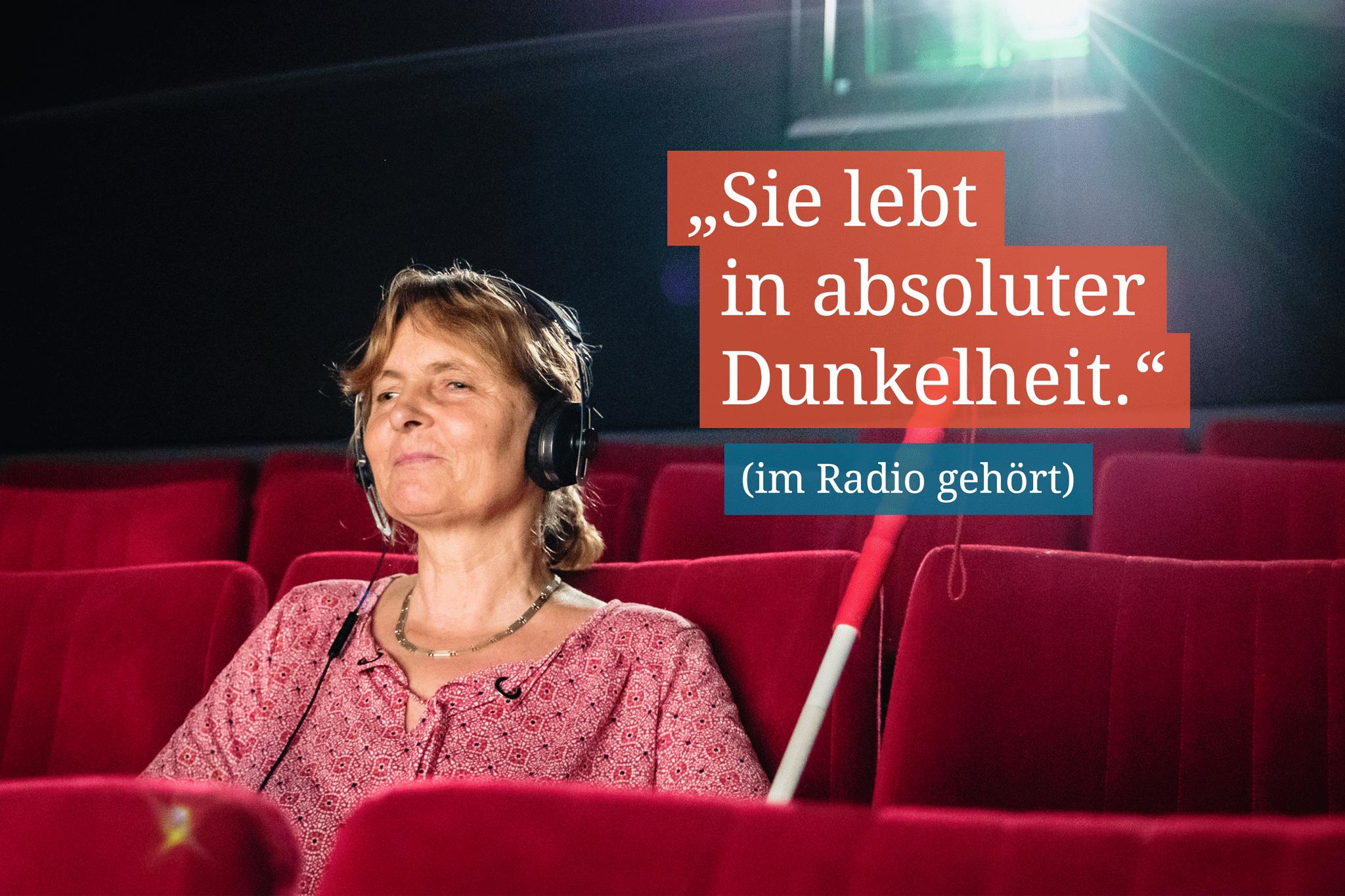 """Eine Frau mit einem Langstock sitzt in einem Kinosaal. Auf einem Text steht: """"Sie lebt in absoluter Dunkelheit."""""""