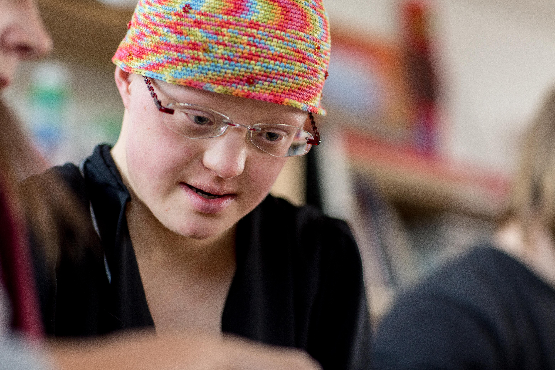 Eine Frau mit Down-Syndrom schaut freundlich nach unten. Sie trägt eine Brille, ein buntes Kopftuch und ein schwarzes Oberteil.