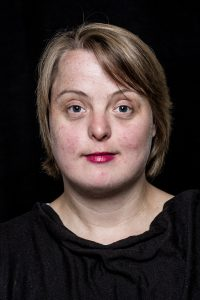Eine Frau mit Down-Syndrom ist bis zu den Schultern zu sehen. Sie hat blonde kurze Haare und trägt ein schwarzes Oberteil. Der Hintergrund ist ebenfalls schwarz.