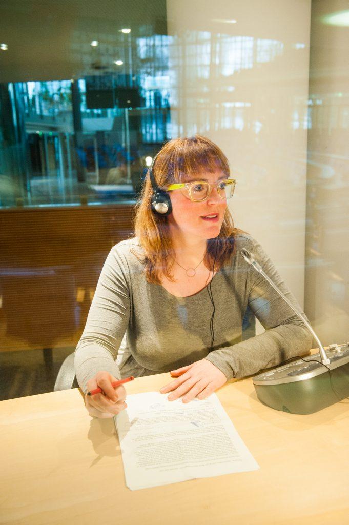 Eine Frau mit langen blonden Haaren und Brille sitzt an einem Tisch hinter einer Glasscheibe. Sie spricht in ein Mikrofon und hat Kopfhörer auf.