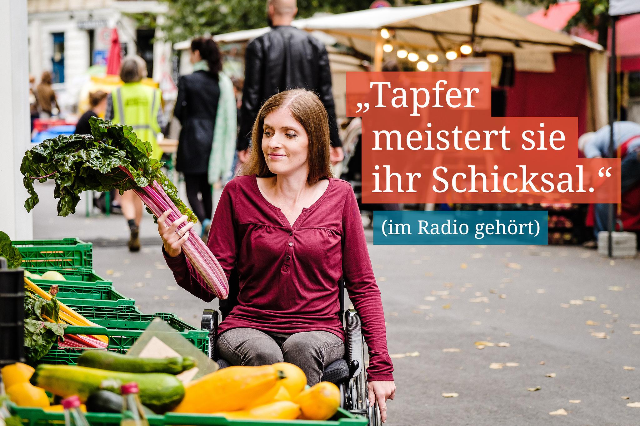 """Eine Frau im Rollstuhl steht an einem Stand auf einen Markt und schaut sich Gemüse an. Daneben steht: """"Tapfer meistert sie ihr Schicksal."""" (im Radio gehört)"""