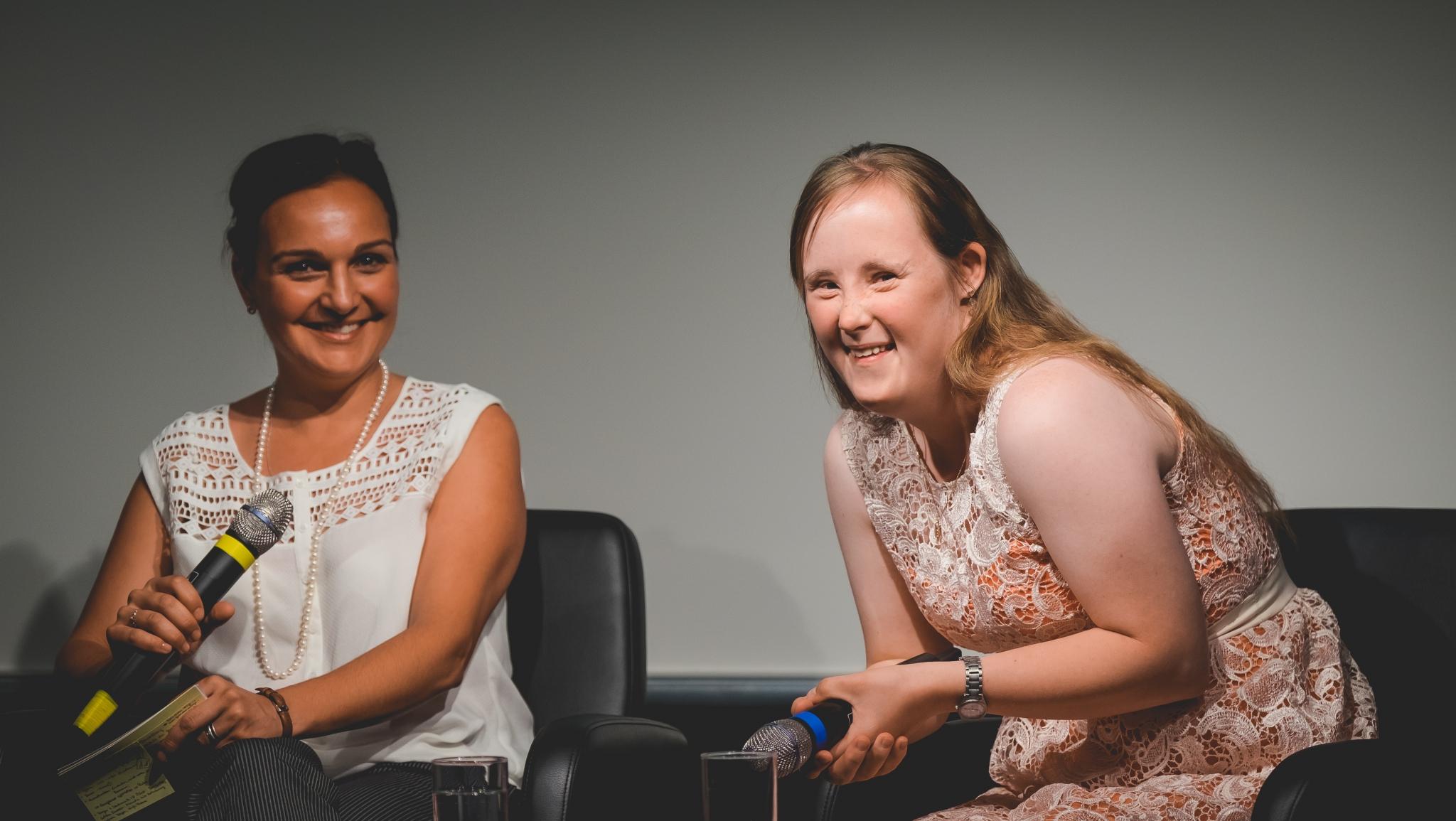 Zwei Frauen sitzen jeweils in einem Sessel und schauen freundlich in die Kamera. Dabei haben beide ein Mikrofon in der Hand.