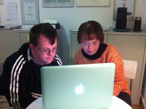 Ein Mann und eine Frau mit Down-Syndrom lesen am Laptop.