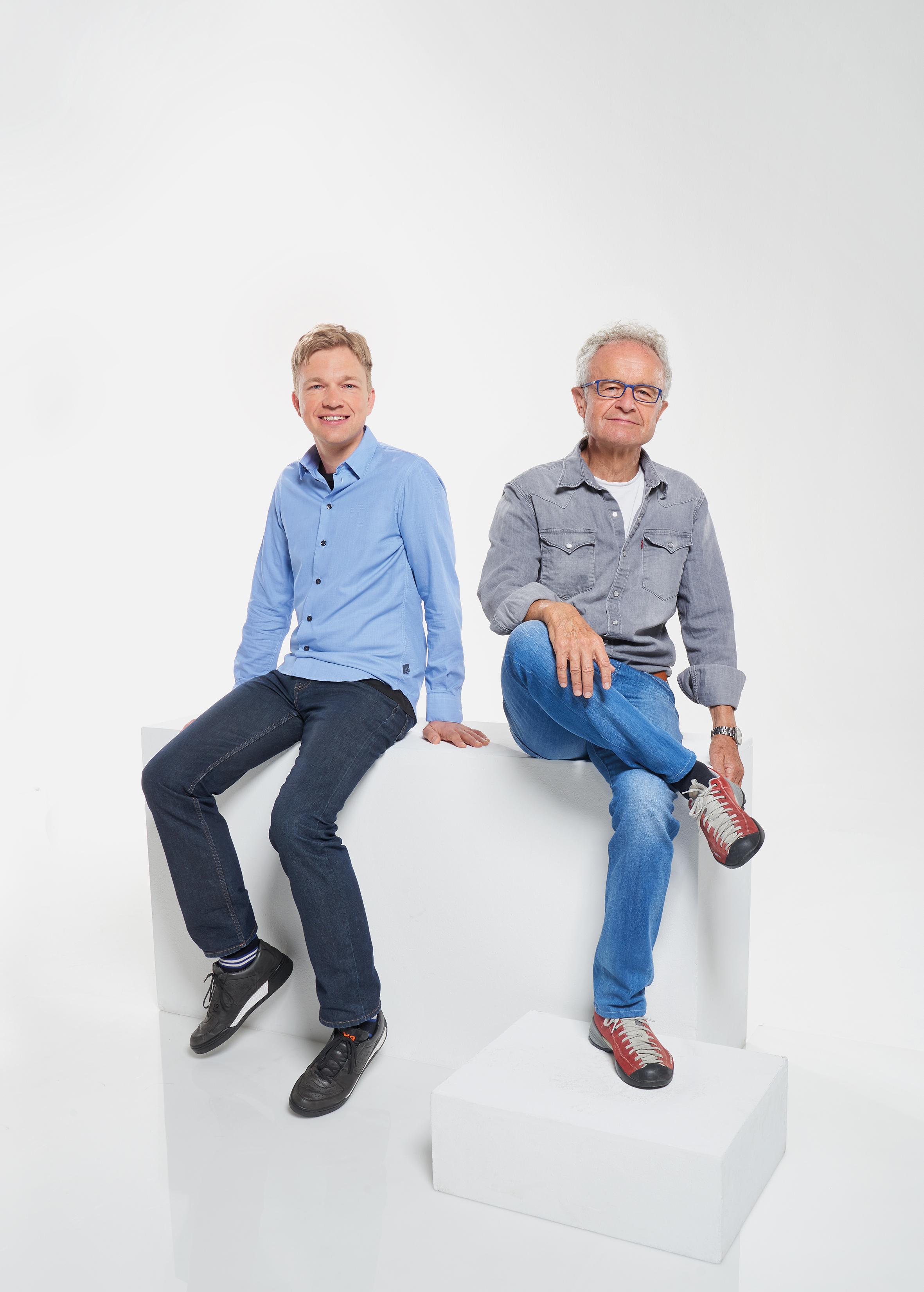 Andreas Croonenbroeck trägt eine dunkle Jeans zu hellblauem Hemd und schwarze Turnschuhe. Er hat blonde kurze Haare und lächelt in die Kamera. Neben ihm sitzt wie er auf einem weißen Klotz Christoph Ammon, der eine helle Jeans trägt zu einem grauen Hemd und roten Turnschuhen. Er hat graue Haare und trägt eine eckige Brille.
