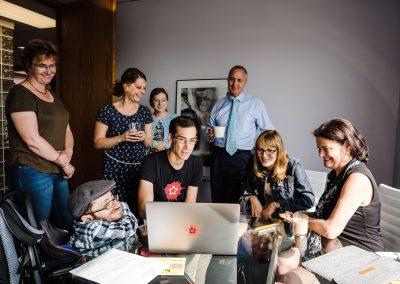 Eine Gruppe von Menschen steht und sitzt vor einem Laptop und schaut darauf.