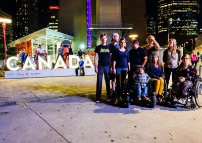 Die Sozialhelden stehen draußen auf einem Platz. Hinter der Gruppe steht auf großen Buchstaben Canada.