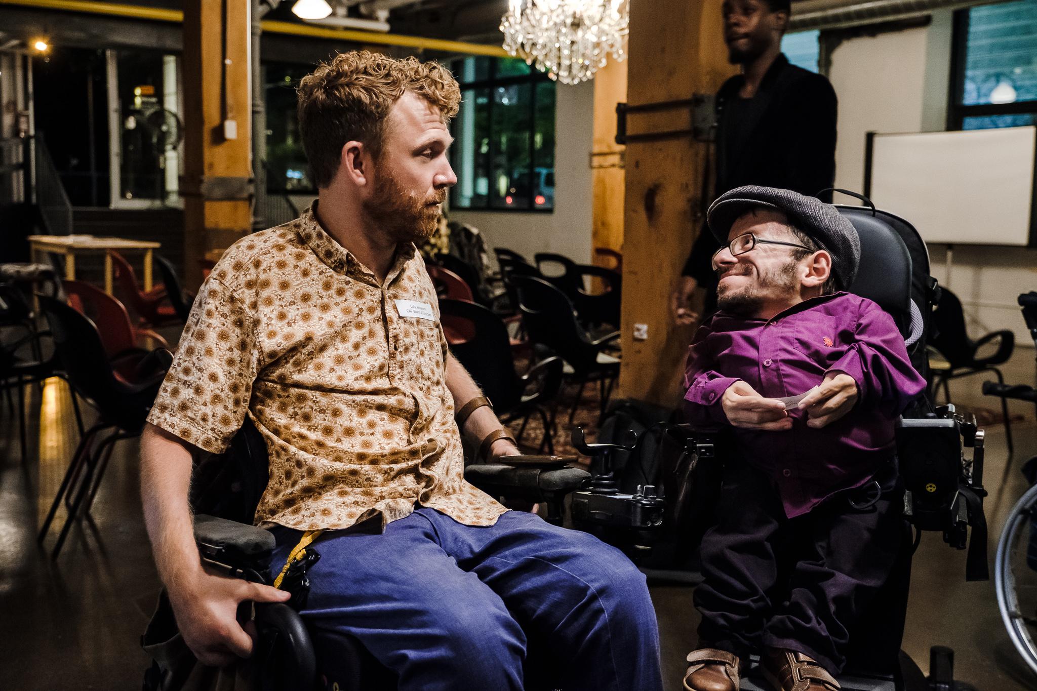 Luke Anderson und Raul Krauthausen unterhalten sich. Beide sitzen im Rollstuhl.