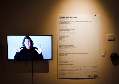 An der Wand ist ein Gedicht, daneben ein Bildschirm mit einer Frau die das Schriftliche gebärdet.