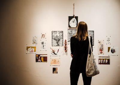 Eine Wand mit Malereien ist zu sehen und eine Frau mit dem Rücken zur Kamera, die sich die Kunstwerke anschaut.