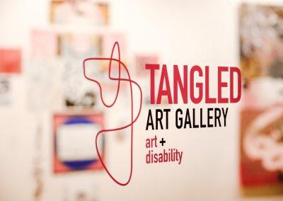 Zu sehen ist das Logo der Tangled Art Gallery. Es besteht aus pinken Linien die verbinden sind. Außerdem der Schriftzug Tangled Art Gallery art+disability.